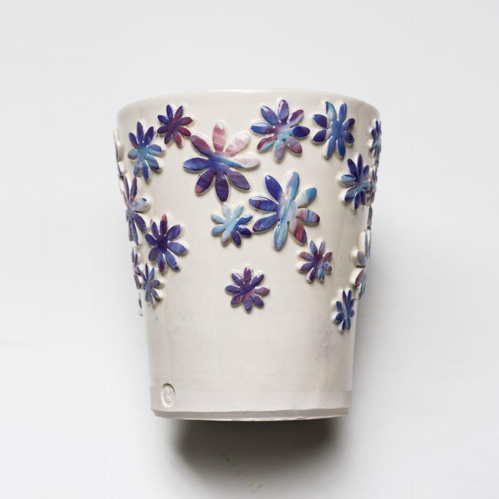 Bote de loza blanca con decoración en relieve y engobes.