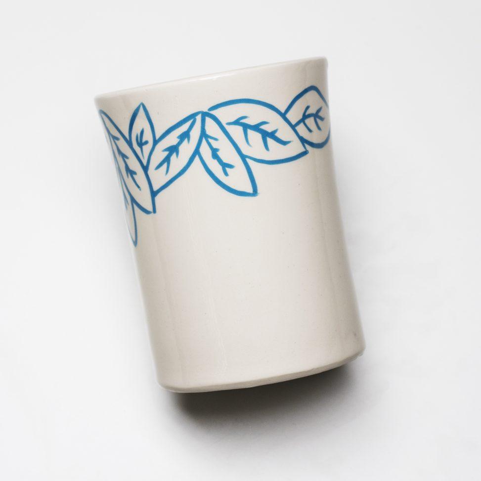 Bote de loza blanca con decoración incisa y engobes.